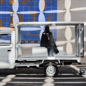Imagen que nos muestra a una mujer completamente vestida de negro en el interior de un camiión cuyas paredes son transparentes